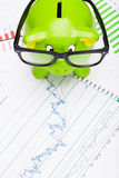 Green piggy bank over stock market chart - view from top Stock Photo
