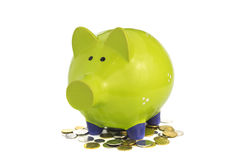 Green piggy bank standing on coins. Isolated over white Royalty Free Stock Images