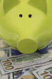 Green piggy bank standing on dollar bills. Close up of green piggy bank standing on a pile of hundred dollar bills Stock Photo