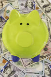 Green piggy bank standing on dollar bills. Close up of green piggy bank standing on a pile of hundred dollar bills Royalty Free Stock Photos