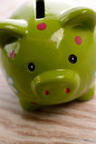 Green piggy bank on a wooden background. Closeup of a green piggy bank Stock Photos