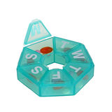 Green pill dispenser in the shape of a wheel. Heptagonal dispenser for a week of pills with the Monday compartment open isolated against a white background stock photo
