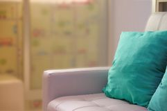 Green pillows on white sofa beside glass door royalty free stock image