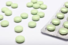 Opioid epidemic and drug abuse concept. Green pills and blister pack on white background. Stock Photo