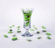 Green pills i ett exponeringsglas Arkivfoton