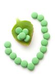 Green Pills and leaf. Green pills and a leaf on white royalty free stock images