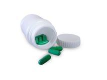 Green pills and pill bottle Stock Photo
