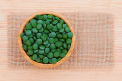 Green pills spirulina and chlorella seaweed close up in a wooden bowl top view with frame. Green pills spirulina and chlorella seaweed close up n the wooden bowl Royalty Free Stock Image