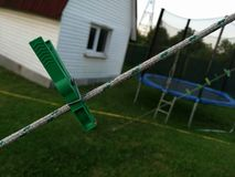 Green pin on rope with house and trampoline in background stock photos