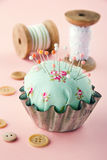 Green pincushion in an old metal cupcake Stock Photo