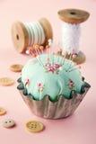 Green pincushion in an old metal cupcake Stock Photo