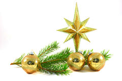 Green pine branch with gold Christmas tree balls and star. Royalty Free Stock Photography