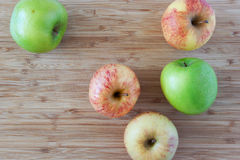 Green and pink apples on wooden background Stock Photo