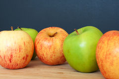 Green and pink apples on a wooden and black background Stock Image