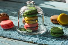 Green, pink, brown and yellow french macarons with mint leaves. Soft focus background Stock Photography