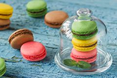 Green, pink, brown and yellow french macarons with mint leaves. Soft focus background Stock Photo