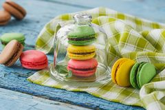 Green, pink, brown and yellow french macarons with mint leaves. Soft focus background Royalty Free Stock Photos