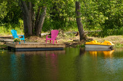 Green and pink chairs on a dock Royalty Free Stock Image