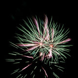 Green and pink fireworks. On black background stock photography