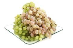 Green and pink grapes on a plate. Royalty Free Stock Photography
