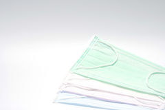Green, pink, light blue and white ear loop disposable face mask overlapping, used for covering mouth and nose. It protects against Stock Photos