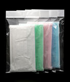 Green, pink, light blue and white ear loop disposable face mask in plastic bag overlapping, used for covering mouth and nose Royalty Free Stock Images