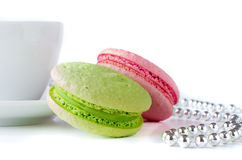 Green and pink macaroons with a cup and silver chaplet Stock Images