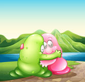 A green and a pink monster hugging each other at the riverbank Royalty Free Stock Images