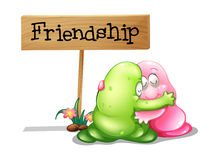 A green and a pink monster hugging near the wooden signage Royalty Free Stock Photography