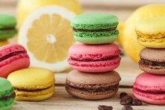 Green, pink, yellow and brown french macarons with lemon and coffee beans. Soft focus background royalty free stock photos
