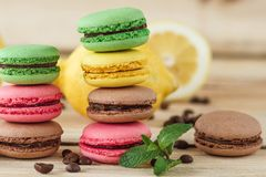 Green, pink, yellow and brown french macarons with lemon and coffee beans. Soft focus background royalty free stock images