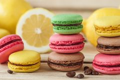 Green, pink, yellow and brown french macarons with lemon and coffee beans. Soft focus background stock photo