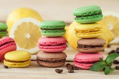 Green, pink, yellow and brown french macarons with lemon and coffee beans. Soft focus background royalty free stock photo