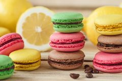 Green, pink, yellow and brown french macarons with lemon and coffee beans. Soft focus background stock image