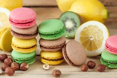 Green, pink, yellow and brown french macarons with lemon, kiwi and hazelnuts. Soft focus background stock photography
