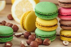 Green, pink, yellow and brown french macarons with lemon, kiwi and hazelnuts. Soft focus background royalty free stock image