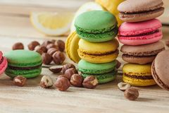 Green, pink, yellow and brown french macarons with lemon, kiwi and hazelnuts. Soft focus background royalty free stock photography