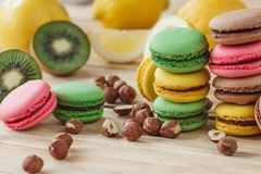 Green, pink, yellow and brown french macarons with lemon, kiwi and hazelnuts. Soft focus background stock images