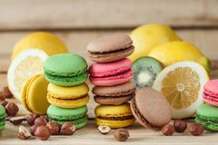 Green, pink, yellow and brown macarons with lemon, kiwi and hazelnuts. Green, pink, yellow and brown french macarons with lemon, kiwi and hazelnuts, soft focus royalty free stock image