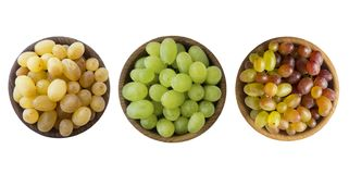 Green, pink and yellow grapes Kishmish. Top view. Grapes in a wooden bowl isolated on white background. Vegetarian or healthy eati stock image