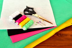 Green, pink, yellow, white and black felt sheets. Scissors, thread and pins on a wooden table Royalty Free Stock Photo