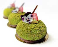 Green desserts with strawberries and edible flowers on golden coasters stock photos