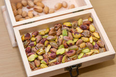 Green pistachio nuts without shell in a wooden box Royalty Free Stock Photos