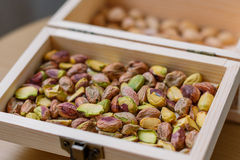 Green pistachio nuts without shell in a wooden box Royalty Free Stock Photography