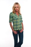 Green plaid. Pretty young blonde woman in a green plaid shirt and jeans Royalty Free Stock Image