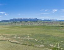 Green Plains and Rocky Mountains. Green plains and farmlands below the high ridges of the Rocky Mountains stock photography