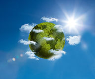 Green planet floating bright blue sky Royalty Free Stock Photography