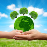 Green planet with trees in hands. Earth day concept Stock Image