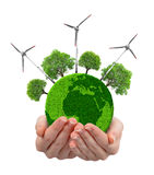 Green planet with trees and wind turbines in hands Stock Photo