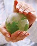 Green planet in women's hands. Royalty Free Stock Photo